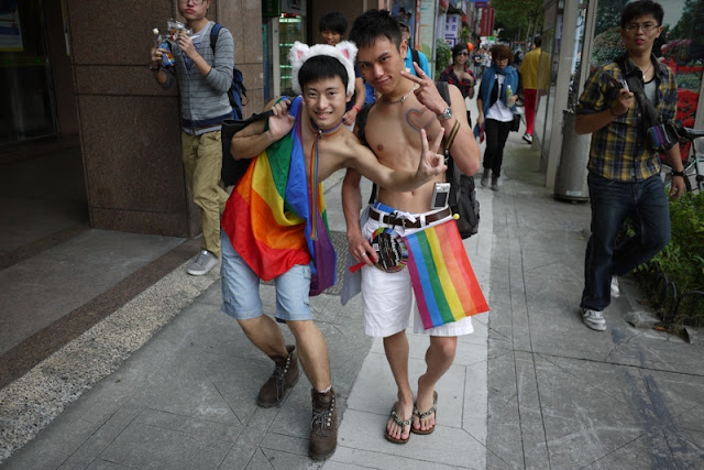 two young men with rainbow flags