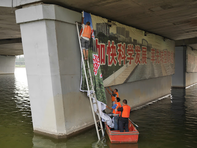 "man on ladder and men in boat covering the slogan ""加快科学发展 率先转型跨越"" with another sign"