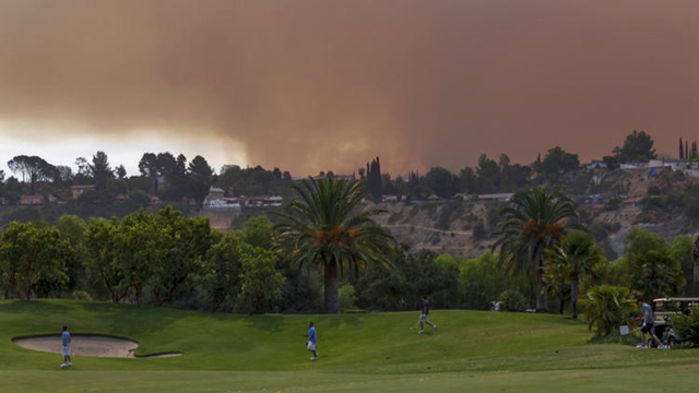 Golfers at Angeles National Golf Course play while the La Tuna fire burns nearby in the Verdugo Hills above Sunland-Tujunga, 2 September 2017. Photo: Irfan Khan / Los Angeles Times