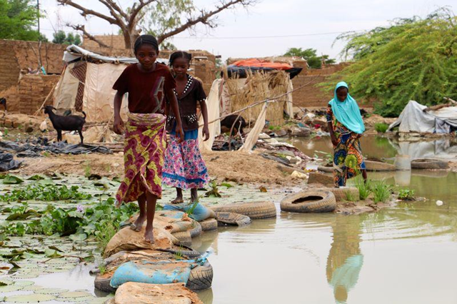 Children walk through a flooded area in Banga Bana district in Niamey, Niger, 9 September 2017. Photo: Morgane Le Cam / Thomson Reuters Foundation