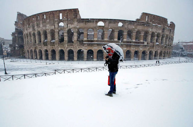A man stands in front of the ancient Colosseum blanketed by the snow in Rome, Monday, 26 February 2018. Photo: Alessandra Tarantino / AP Photo