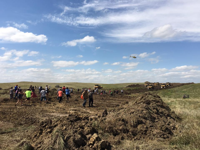 Standing Rock Sioux Tribe protesters confront Energy Transfer Partners workers and earth-moving equipment that desecrated sacred burial grounds on 3 September 2016. Photo: Native News Online