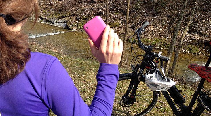 Annas Farbkontraste: lila Trikot, pinkes Handy, weißer Fahrrad-Helm, schwarzes Rad, roter Erdbeer-Sattel