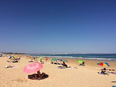 Parasoller spredt utover sanden på en lang og bred strand.