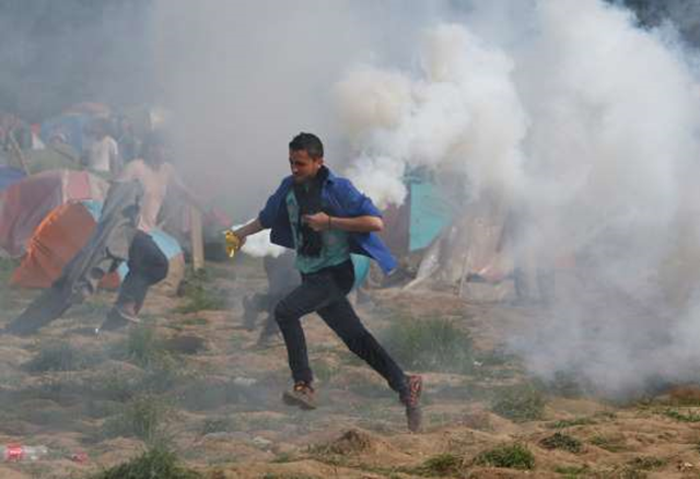 Migrant man runs with a tear gas canister during clashes with Macedonian police during a protest at a fence at the northern Greek border point of Idomeni, Greece, Sunday, 10 April 2016. Some thousands of migrants protested at the border and clashed with Macedonian police. Photo: Amel Emric / AP Photo