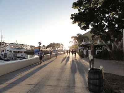Gangvei langs en havn med sola midt i mot.
