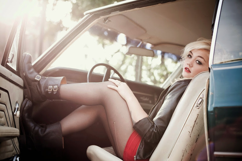 Elle King sitting in a vintage car with her feet on the door, in biker boots and leather jacket.