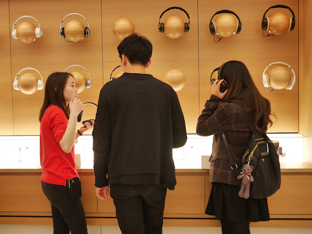 Apple employee assisting a customer with headphones at the SM Lifestyle Center Apple Store in Xiamen, China