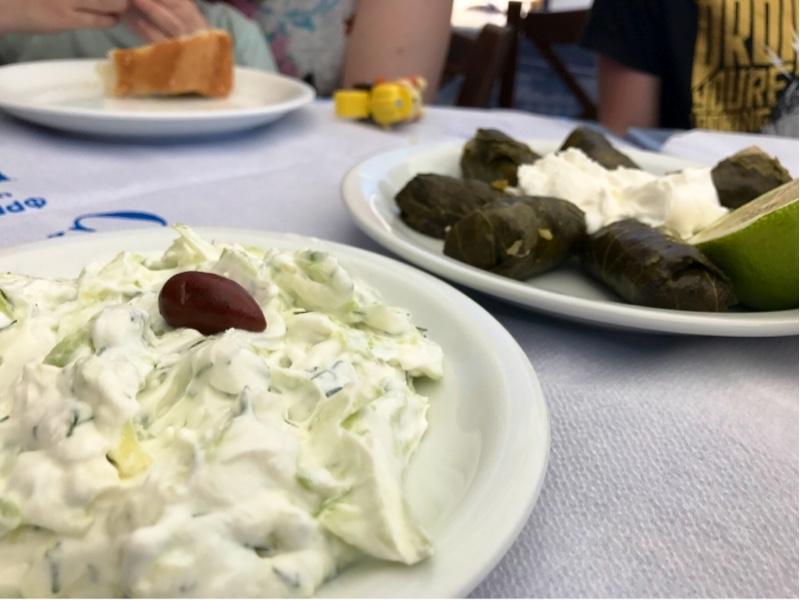 En skål med tsakiki toppet med en oliven til venstre. Til høyre et fat med mørkegrønne fylte vinblader med naturell yoghurt.