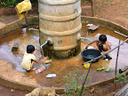 Children washing clothes and old bottles
