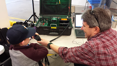 ARRL Sacramento Valley Section Youth Coordinator, Orion Endres, AI6JB, coaches a young STEM Expo attendee at the VHF Station