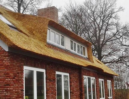 Ceglany domek pokryty żółtym dachem trzcinowym