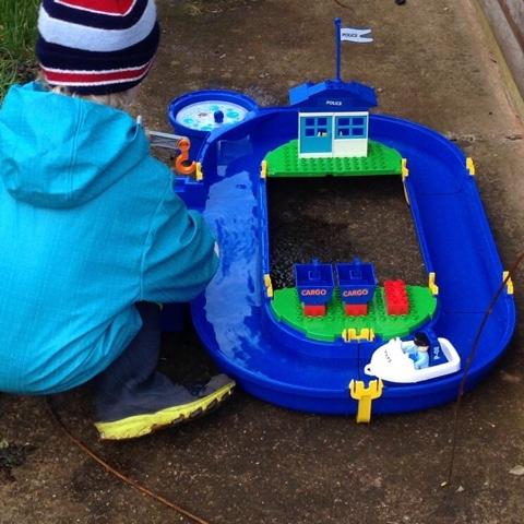 Kind spielt mit Wasserbahn