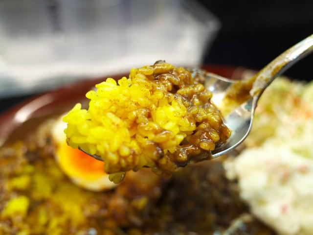 黄色いサフランライスのようなご飯とカレーをスプーンですくってみた