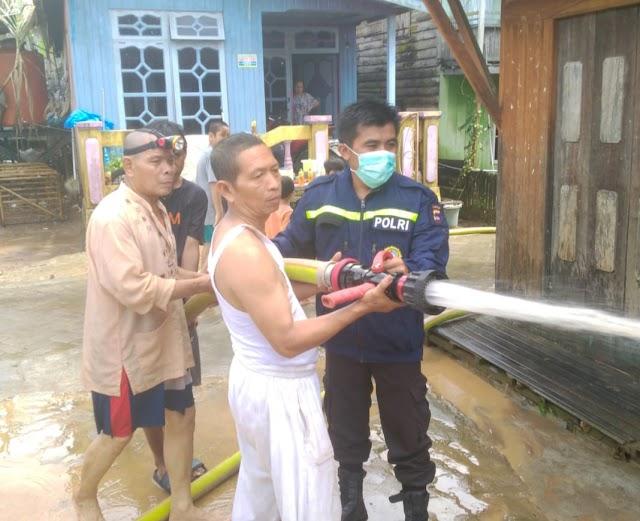 Bersama Warga Desa, Bhabinkamtibmas Bersihkan Rumah Terendam Banjir