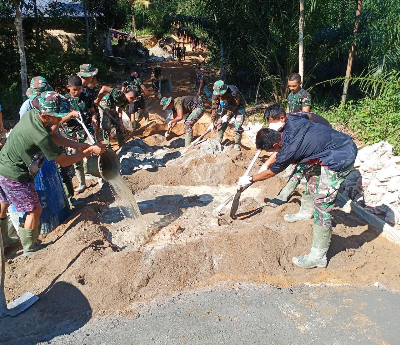 Anggota TMMD satgas terus pacu Semanggat saat mengadon semen bersama warga