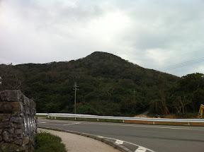 駐車場右手に今帰仁城跡の入口(画面左)。道路は県道115号線