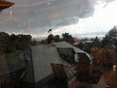 Storm clouds over a wet Champlain College campus, as viewed through a rain-spattered window.
