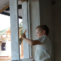 Josh helps paint a window frame.