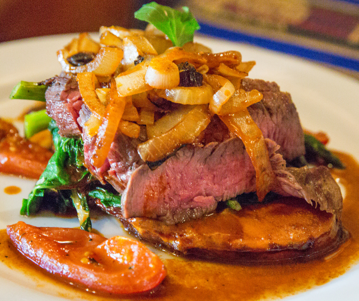 photo of steak topped with caramelized onions