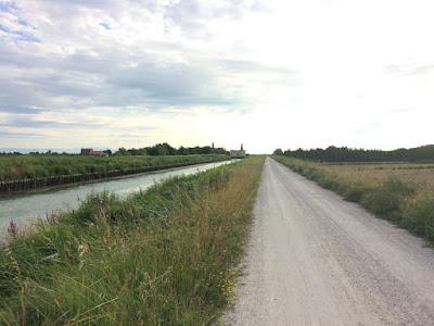 En grusvei som går langs en kanal.
