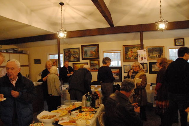 Guests enjoy refreshments while viewing art and speaking with the artists behind the works.