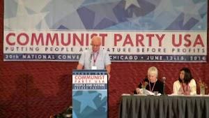 Rednerpult und Podium, drei Personen. Transparent «Communist Party USA...».