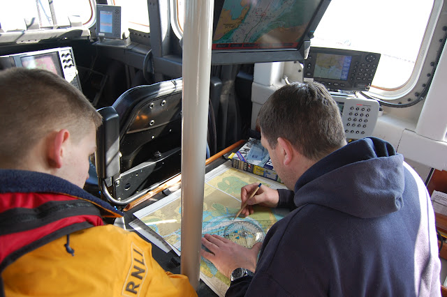 Mechanic Paul Taylor at the chart table with new crew member Anthony Skerman, on an Easter Sunday training exercise - 31st March 2013. Photo credit: RNLI Poole/Dave Riley