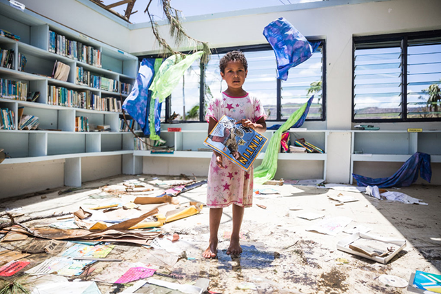 In the aftermath of Cyclone Winston, a seven-year old girl stands in the destroyed library of Nabau District School in Ra Province, Fiji. Photo: UNICEF / UN011701 / Sokhin