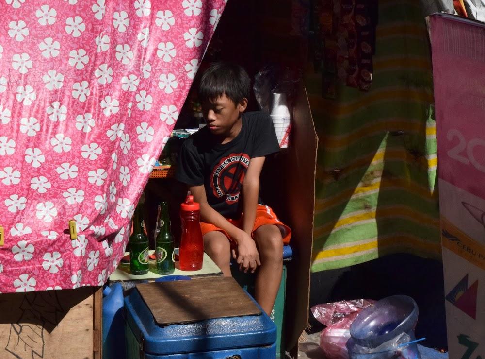 a poor boy working a sidewalk stall