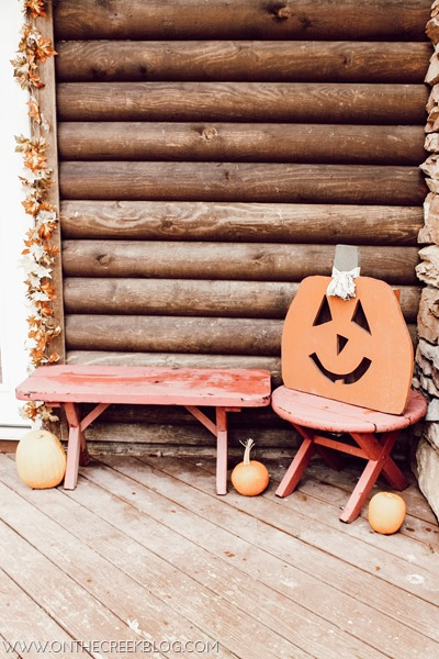Simple fall porch with small pumpkins & wooden carved pumpkin