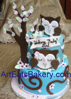 Two tier blue fondant baby shower cake with brown sugar paste owls, tree and pink flowers