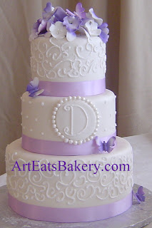 Three tier unique white fondant wedding cake with monogram, curlicue design, purple flowers, buttterflies and ribbons