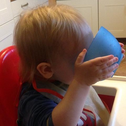 Kind trinkt Milch aus Schüssel
