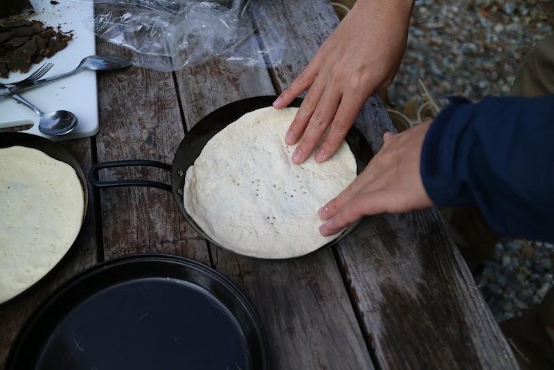ピザ生地を鉄板に敷いていく