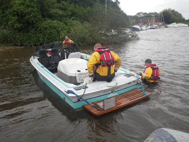 8 June 2012: ILB crew members aboard and alongside the grounded speedboat. Photo: RNLI Poole/Dave Riley