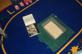 A book and a tub of sand are part of learning about crater formation.