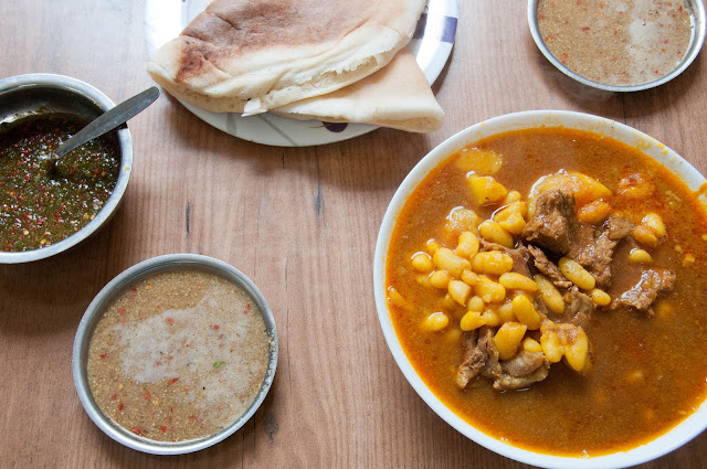 Yemenite beef stew with lachooch bread, hilbeh and schoog