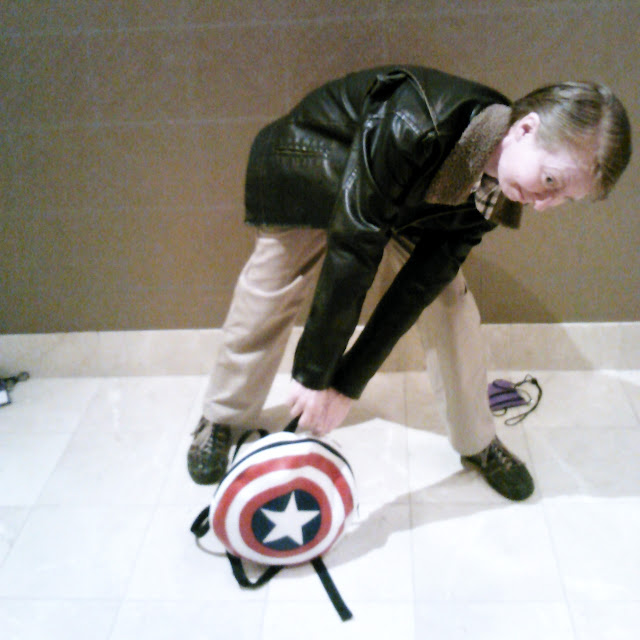Me dressed as Steve Rogers trying in vain to lift a shield-shaped backpack