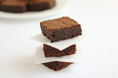 photo of a stack of three brownies with parchment inbetween