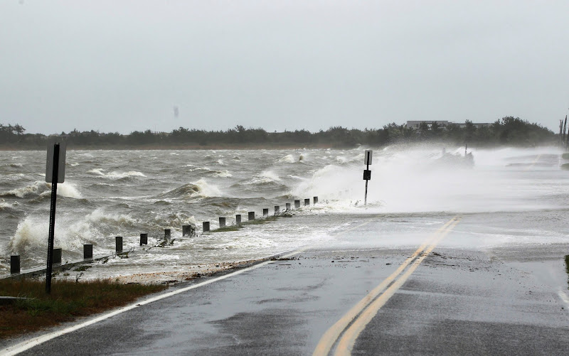 Photo: Waves crest over a road by winds caused by Hurricane Sandy in Southampton, New York.