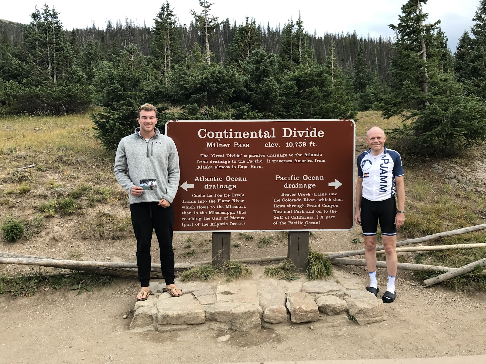Cyclist at Trail Ridge Continental Divide sign.