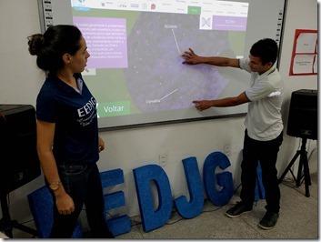 Professora e aluno usando lousa digital