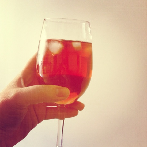 A picture of a wine glass, filled with pink wine and ice cubes.