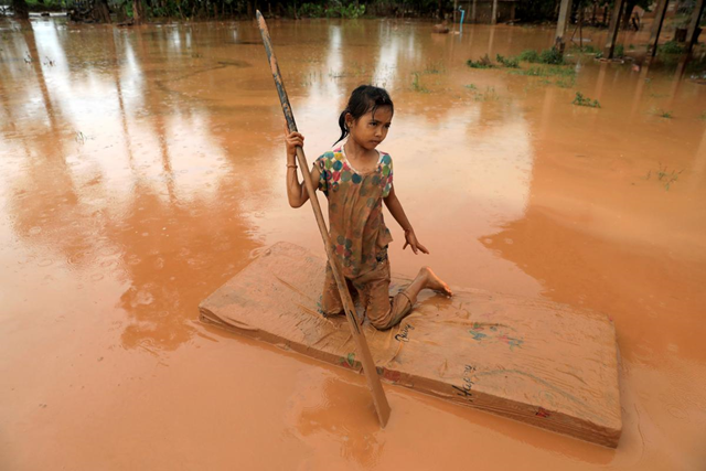 A girl uses a mattress as a raft during the flood after the Xepian-Xe Nam Noy hydropower dam collapsed in Attapeu province, Laos, 26 July 2018. Photo: Soe Zeya Tun / REUTERS