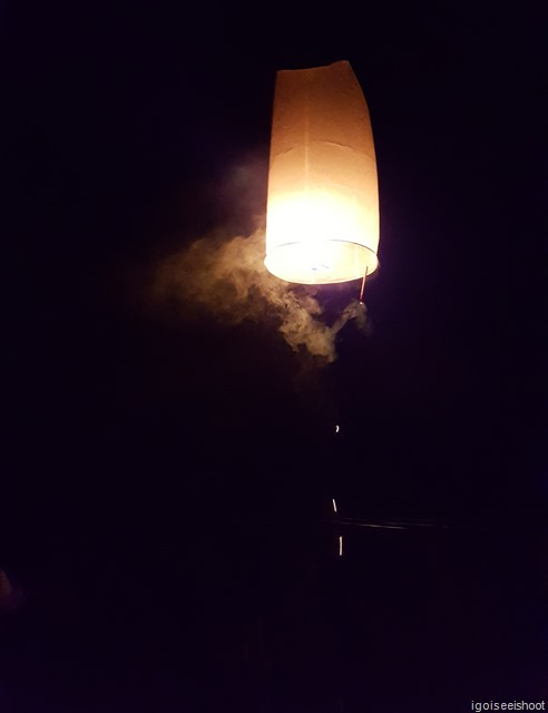 A sky lantern with the burning solid fuel and a small lit firework attached to give it an extra boost halfway during the flight.