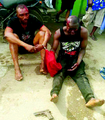Robbers attacking customers, who had gone to withdraw money from banks at Sadiku/ Ilasamaja, along the Oshodi-Apapa expressway, Lagos