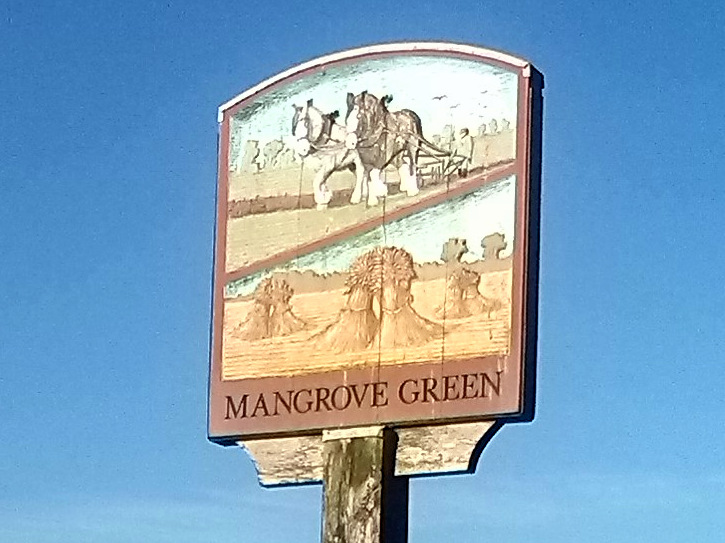 Village sign with horses ploughing