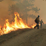 Firefighters start a controlled fire to burn up excess fuel and prevent the spread of wildfires.