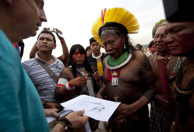 Legendary Chief Raoni receives a banner sketch from artist John Quigley before nearly 1500 people used Rio's Flamengo Beach as a canvas on June 19, 2012. Their bodies formed the lines of an enormous image promoting the importance of free-running rivers, truly clean energy sources like solar power and including indigenous knowledge as part of the solution to climate issues. The activity was led by Brazil's many indigenous peoples organized under the umbrella of the Articulation of Brazilian Indigenous Peoples. ©Caroline Bennett